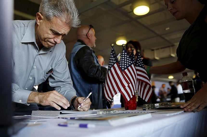 A job seeker filling out papers at a military job fair in San Francisco. All eyes are now on Friday's release of US employment figures, a major indicator used by the Fed to gauge the state of the US economy.