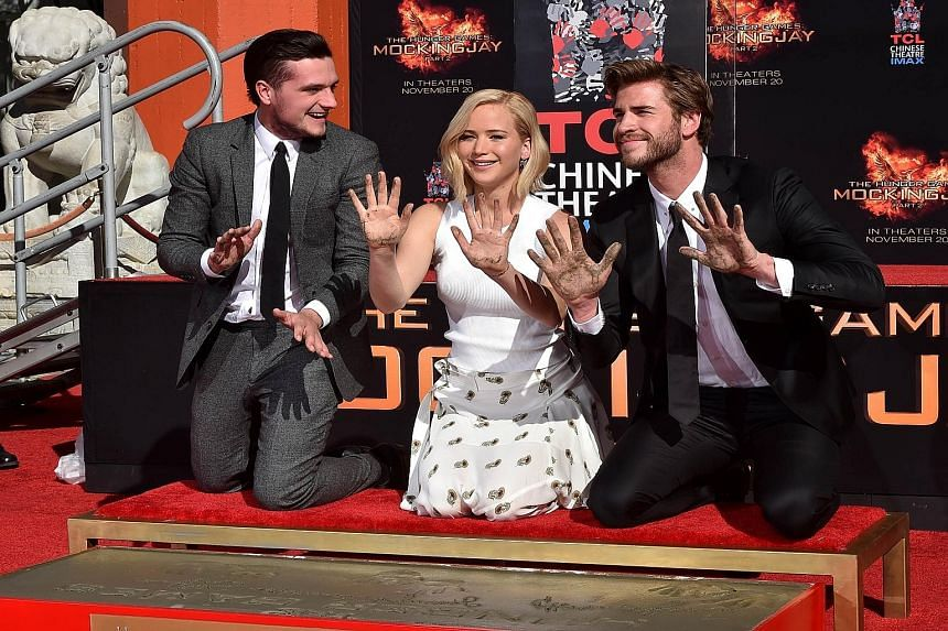 Actress Jennifer Lawrence (centre) with co-stars Josh Hutcherson (far left) and Liam Hemsworth (left) attending the Hunger Games: Mockingjay - Part 2 hand and foot print ceremony at the TCL Chinese Theatre in California last Saturday.