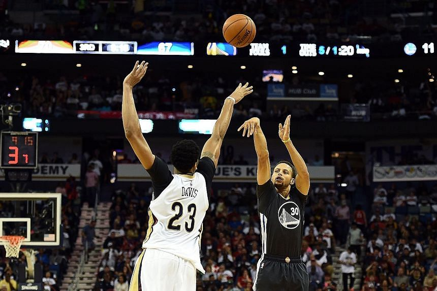 Stephen Curry (right) of the Golden State Warriors takes a three-point shot over Anthony Davis of the New Orleans Pelicans on Saturday. Curry's fluent 53 points in the game led the undefeated Warriors to a 134-120 win.