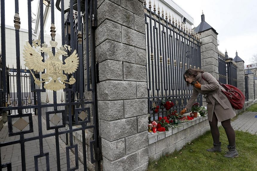 A woman leaving flowers for victims of the plane crash, outside the Russian Embassy in Minsk, Belarus, yesterday. In Russia, flags flew at half mast on the Parliament building, in the Kremlin and on other official buildings. Russian investigators exa