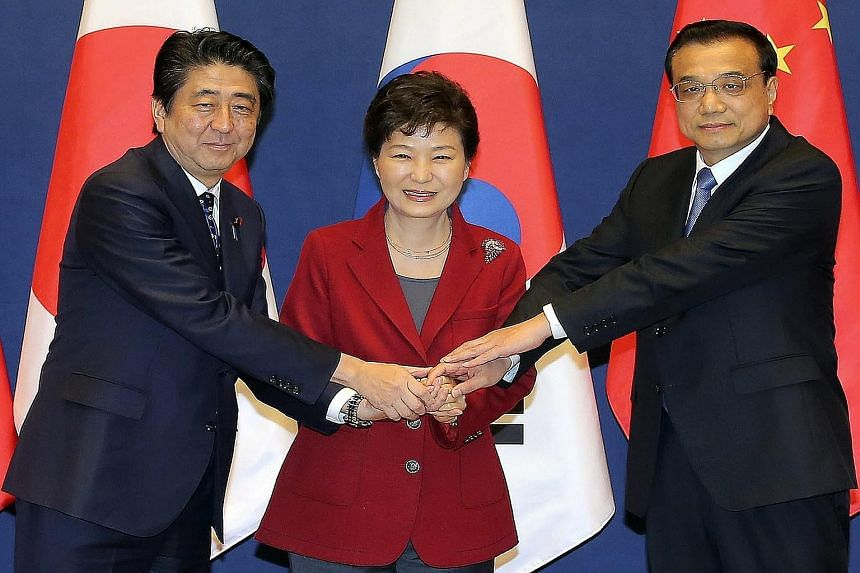 South Korean President Park Geun Hye (centre), Japanese Prime Minister Shinzo Abe (left) and Chinese Premier Li Keqiang at Cheong Wa Dae, the presidential office in Seoul, yesterday.