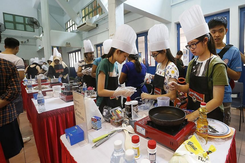 Participants at a dessert-making competition at Geylang Serai Community Club yesterday. Marine Parade GRC MP Fatimah Lateef said, on the sidelines of the event, that she is training grassroots leaders to explain the new healthcare policy to residents