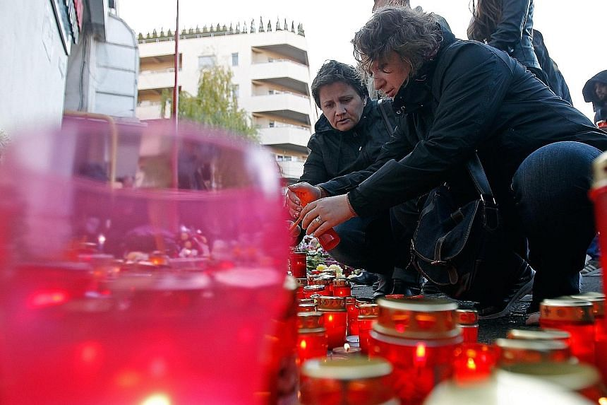 Romanians paying their respects to the blaze victims in front of the nightclub in Bucharest, Romania. The fire, triggered by fireworks let off during a pre-Halloween gig by a band, left 27 people dead and nearly 200 injured.