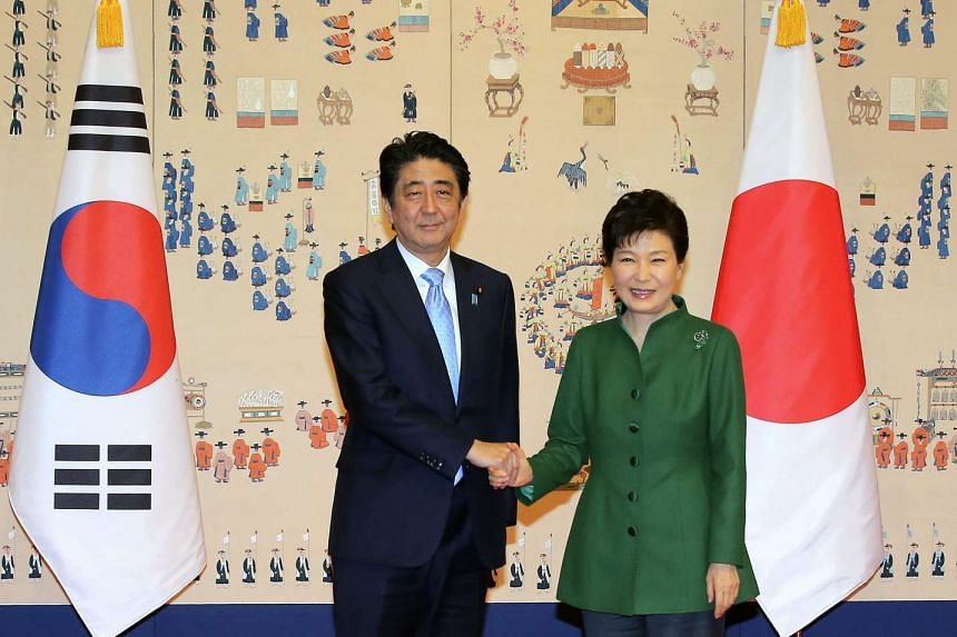 Japanese Prime Minister Shinzo Abe (left) and South Korean President Park Geun Hye shake hands prior to their summit talks at the presidential office in Seoul, South Korea, on Nov 2, 2015.
