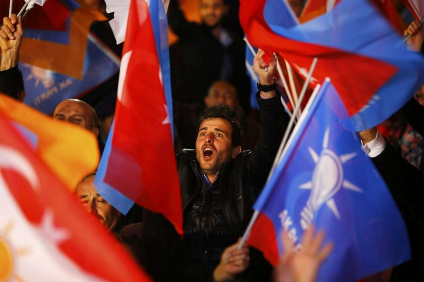 People wave flags outside the AK Party headquarters in Ankara, Turkey, on Nov 1, 2015.