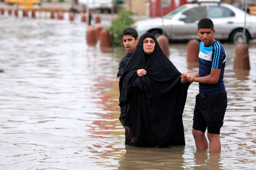 Iraqi youths help a woman cross a flooded street after heavy rainfall in the capital Baghdad, on Oct 29, 2015.