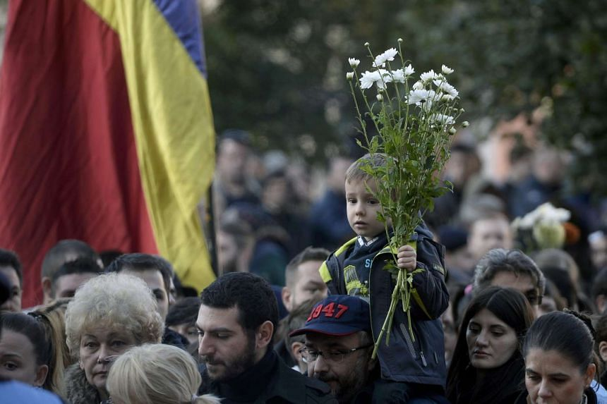 A child carries flowers as thousands of people march silently to commemorate the blaze victims.