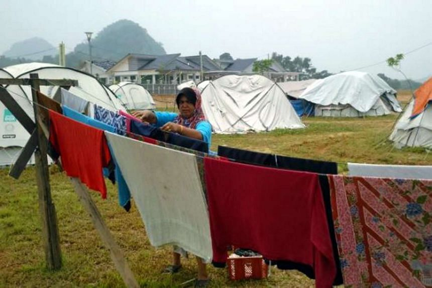 A flood victim hanging clothes at a temporary camp in Kelantan. The monsoon season has begun, with the first heavy rains expected in the first week of November.
