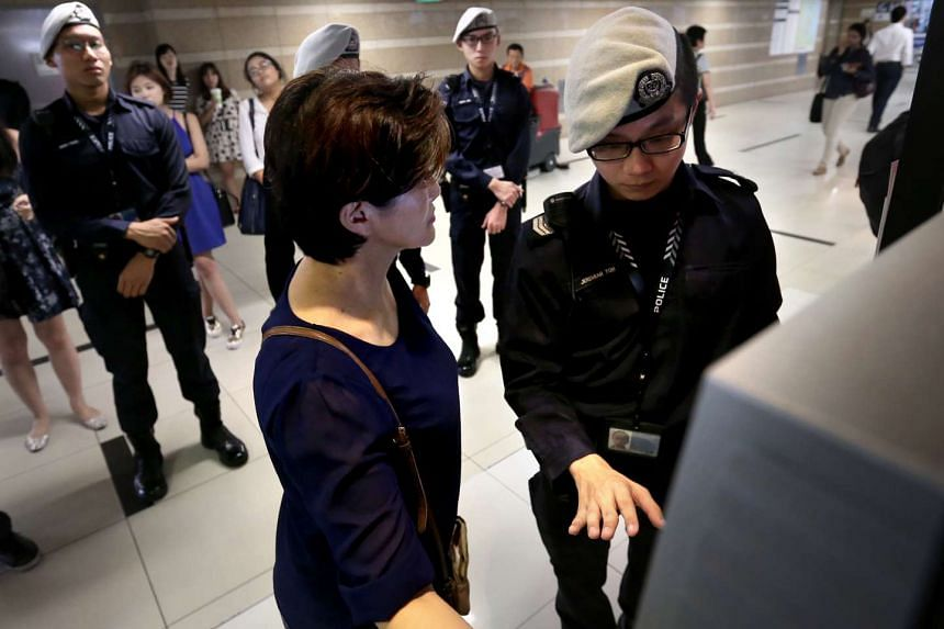 """Special Constable Sergeant Jeremiah Koh trying to stop Madam Lee from transferring money to the """"kidnapper""""."""