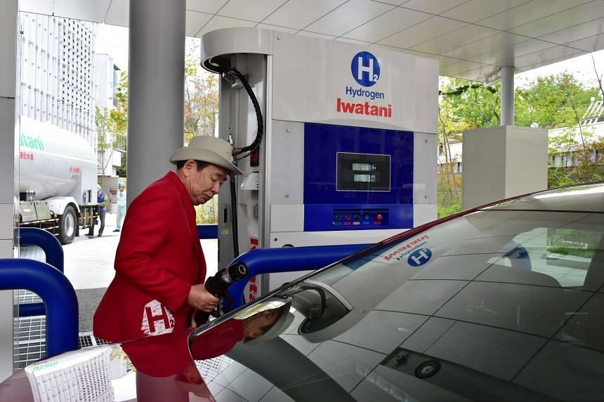 A man topping up a Toyata Mirai fuel cell vehicle with hydrogen gas in Tokyo on Oct 29, 2015.