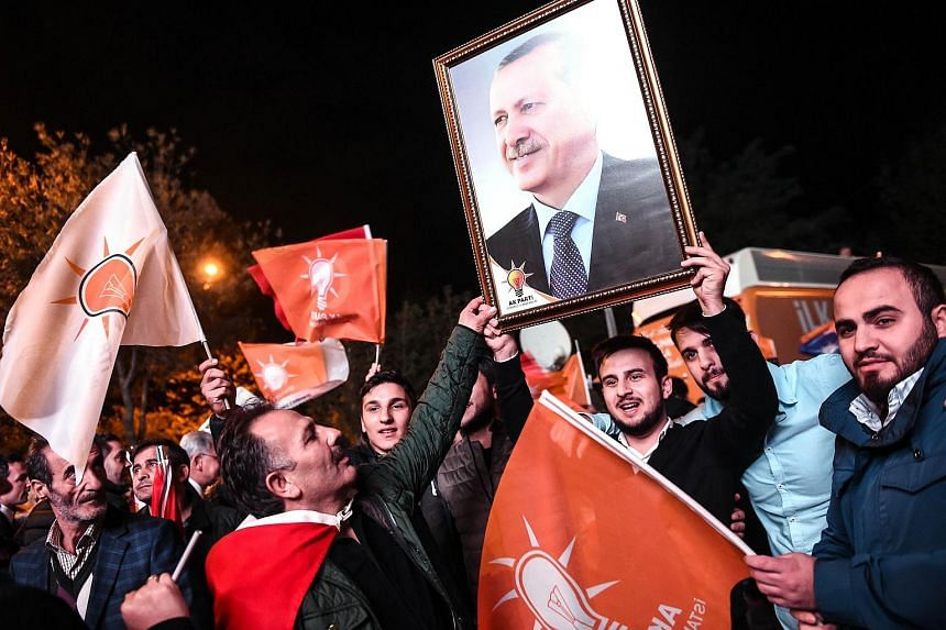 Supporters of Turkey's Justice and Development Party (AKP) hold up a portrait of Turkish President Recep Tayyip Erdogan.