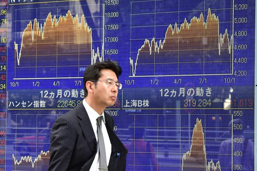 A businessman walks past a share prices board illustrating various world stock markets in Tokyo on Oct 9, 2015.