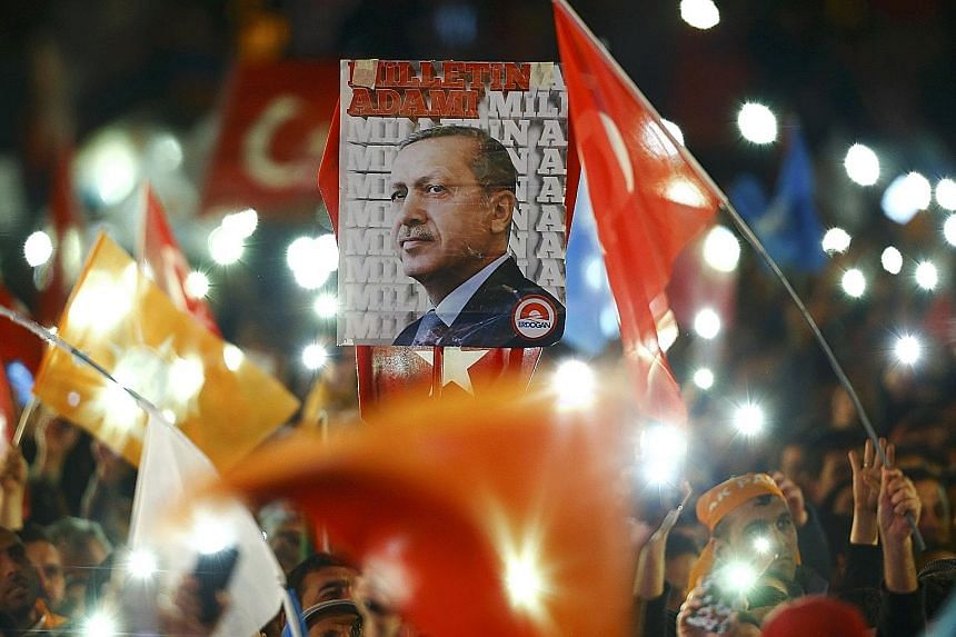 Turks waving flags and displaying a portrait of President Recep Tayyip Erdogan in Ankara yesterday, after the ruling party's surprise advance.
