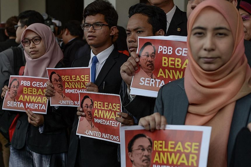 """Malaysian opposition members displaying placards that say """"Release Anwar immediately"""" after a press conference on the UN body's opinion on Anwar Ibrahim at Parliament House in Kuala Lumpur yesterday."""