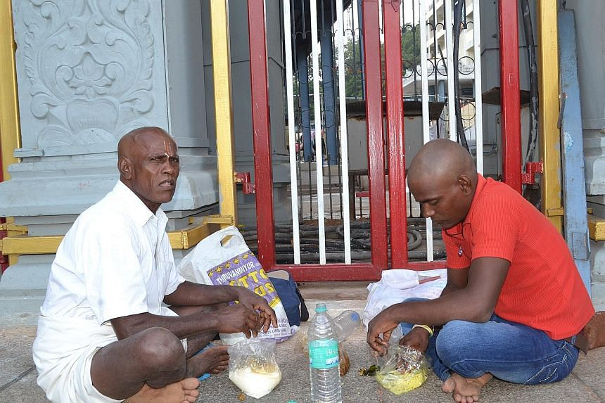 Mr T. Muthu (left), a businessman, eating breakfast with his son, Shanmugam, after offering prayers at the the temple. The waiting time to offer prayers can be up to 16 hours.