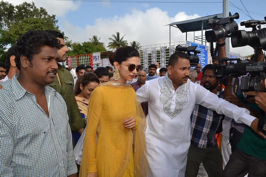 Bollywood actress Deepika Padukone visiting the temple on Thursday. She was mobbed by reporters and cameramen as devotees looked on. Mr T. Muthu (left), a businessman, eating breakfast with his son, Shanmugam, after offering prayers at the the temple