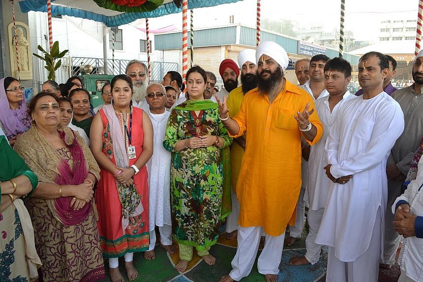 The spiritual head of Sachkhand Nanak Dham, Sant Trilochan Darshan Das (in orange), from the northern state of Punjab, with a group of his followers at the temple last Thursday.