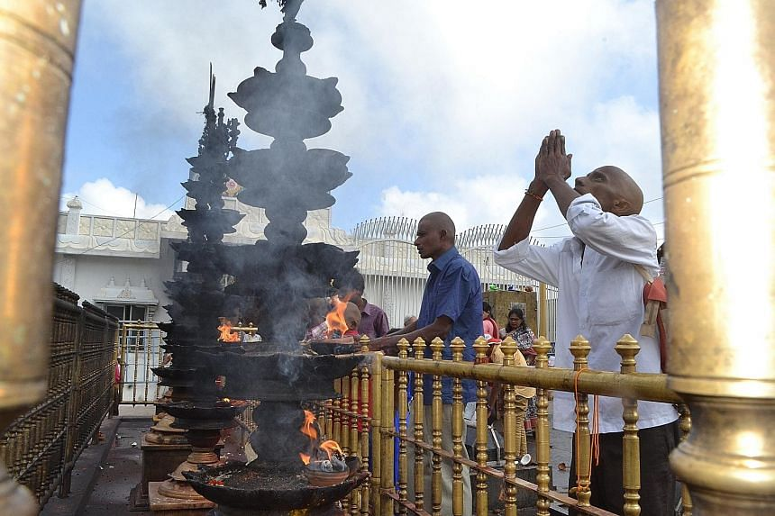 A devotee lights a lamp and offers prayers outside the main temple.