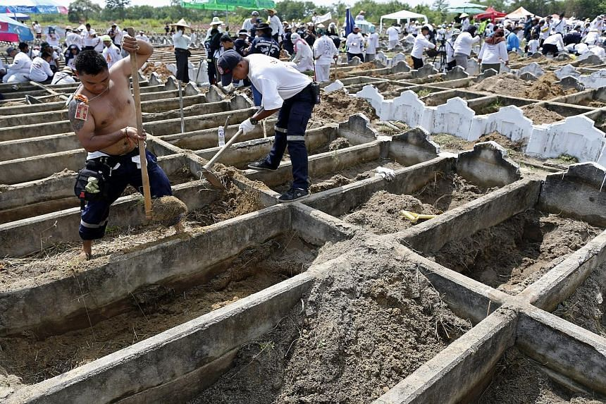 Volunteers digging up unidentified bodies during a mass exhumation at Poh Teck Tung Foundation Cemetery in Samut Sakhon province, Thailand, on Friday. The remains of 3,890 people have been retrieved and they will be cleansed before they are stored in