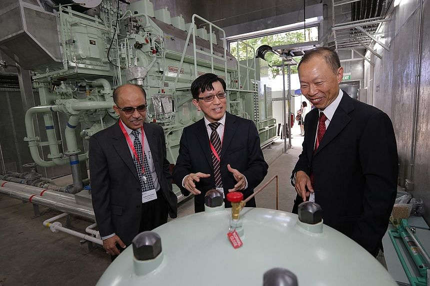 (From left) Singapore Maritime Academy director Mohd Salleh Ahmad Sarwan, Energy Research Institute co-director Chan Siew Hwa and Singapore Polytechnic deputy principal Lim Peng Hun beside the diesel ship engine, which is part of the maritime energy