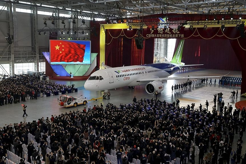 Comac unveiling its first C-919 passenger jet during a news conference at the company's factory in Shanghai yesterday. The plane represents China's efforts to reduce dependence on Airbus and Boeing.