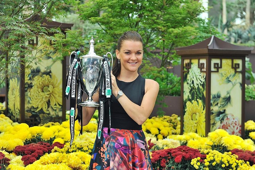 Agnieszka Radwanska posing with the Billie Jean King trophy inside the Gardens by the Bay's Flower Dome yesterday. The 26-year-old won the BNP Paribas WTA Finals Singapore presented by SC Global event on Sunday night, beating Petra Kvitova 6-2, 4-6,