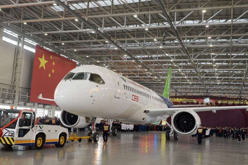 Workers roll out the first C919 passenger jet plane.
