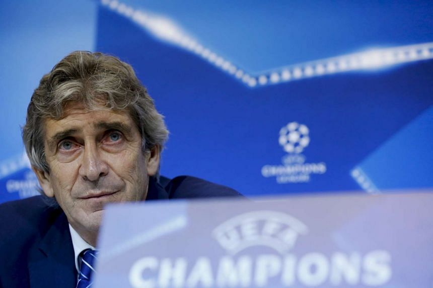 Manuel Pellegrini listens to a journalist during a news conference.