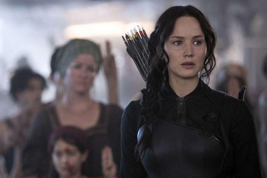 A cinema still from The Hunger Games: Mockingjay - Part 1, starring Jennifer Lawrence as Katniss Everdeen (right).