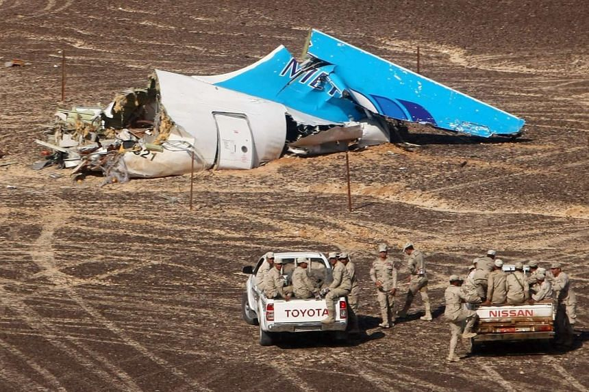 Egyptian servicemen approach a piece of wreckage of the Russian MetroJet Airbus A321.