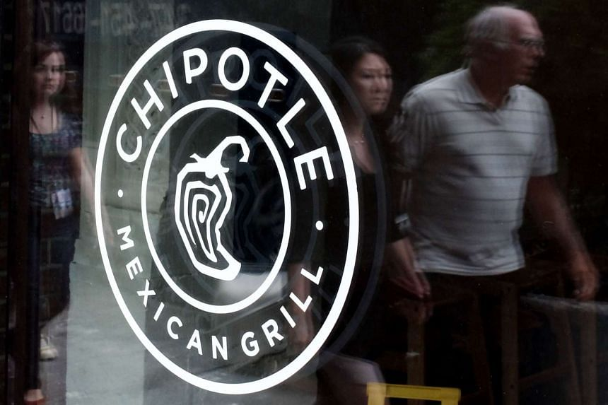 People pass walk by a Chipotle Restaurant in Manhattan on Sept 11 in New York.