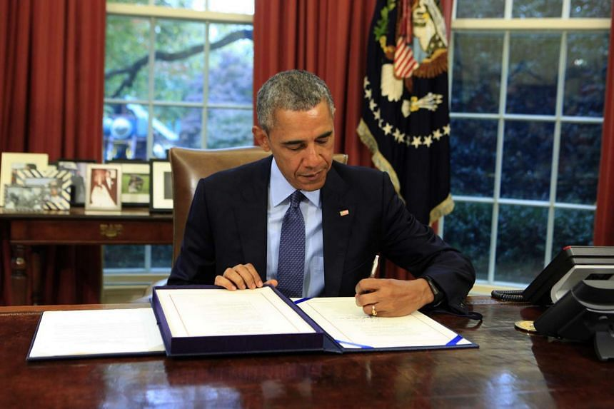 US President Barack Obama signs the bipartisan budget bill 2015 into law in the Oval Office of the White House, in Washington, DC on Monday