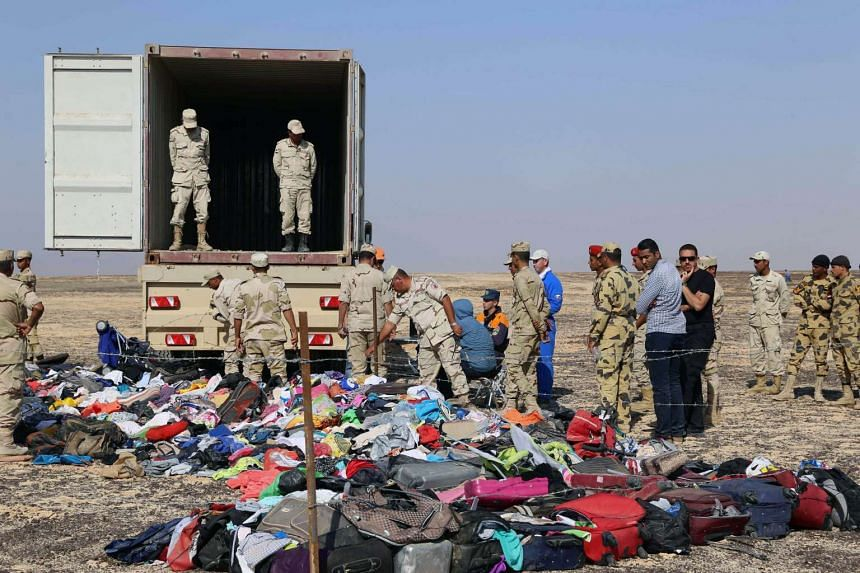 Russian emergency services personnel and Egyptian servicemen working at the crash site of a  Russian airliner in  Egypt's Sinai Peninsula.