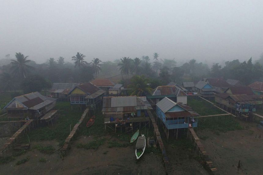 Village houses stand shrouded in haze in Palembang, South Sumatra, Indonesia, on Friday, Oct 30, 2015, but conditions have improved.