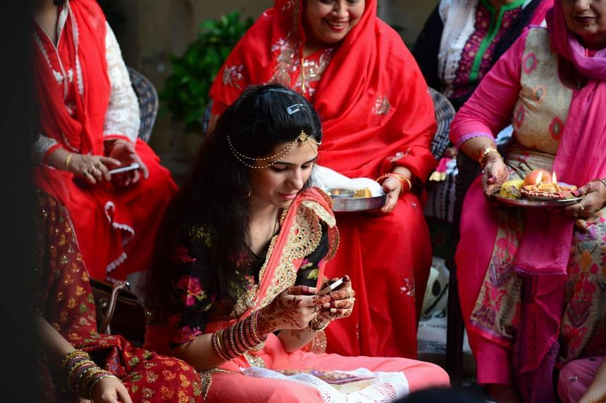 An Indian married Hindu woman texts on her mobile phone as married women perform rituals during the Karwa Chauth festival in Allahabad on October 30, 2015. Karwa Chauth is a traditional Hindu festival celebrated in northern India during which married