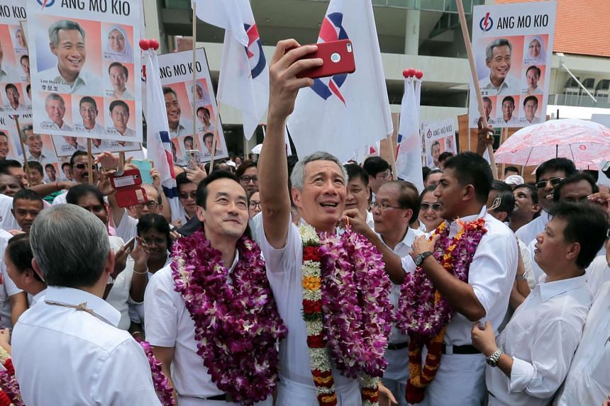 Prime Minister Lee Hsien Loong taking a selfie with his Ang Mo Kio GRC team at Raffles Institution on Sept 1, 2015.