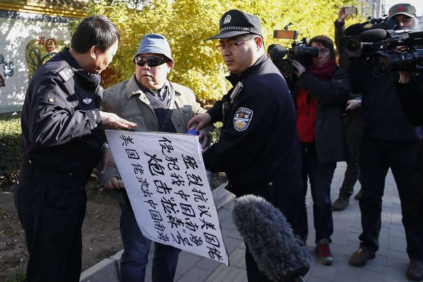 A Chinese protester demonstrating against US encroachment in the South China Sea is confronted by Chinese police officers in Beijing, on Oct 28, 2015.