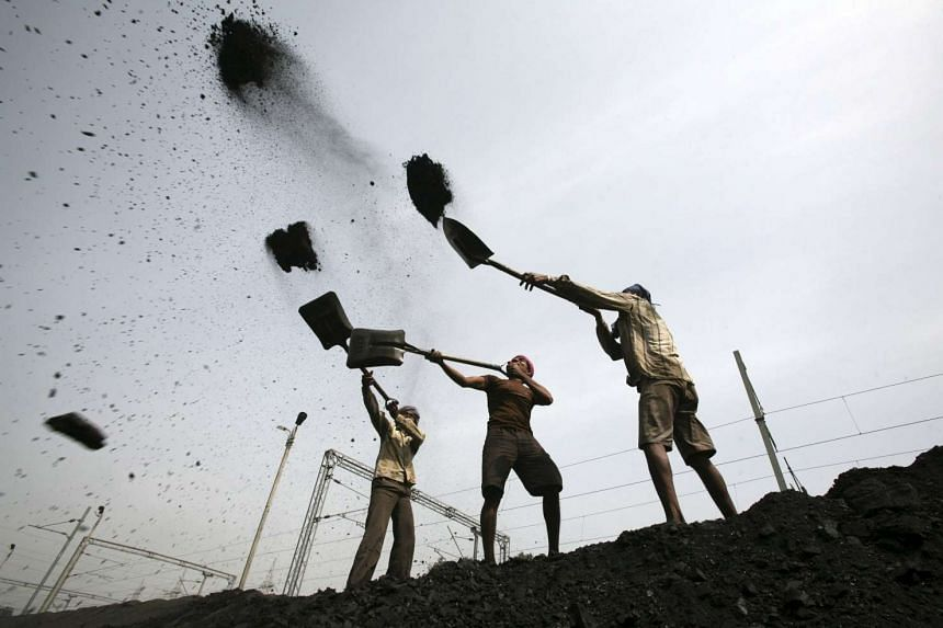 Labourers loading coal on to trucks. China coal consumption statistics have been revised upwards by hundreds of millions of tonnes a year.