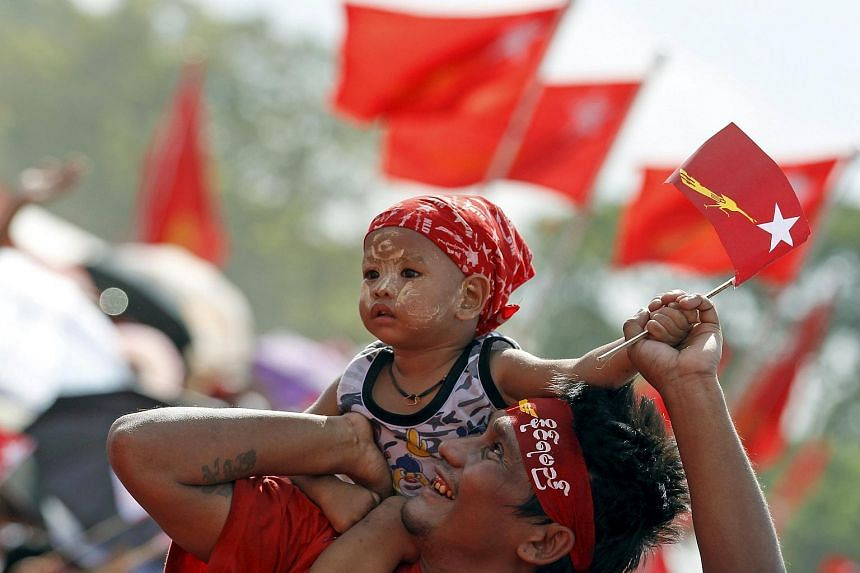 A supporter carrying his baby as Myanmar pro-democracy leader Aung San Suu Kyi speaks at a rally in Yangon on Nov 1.