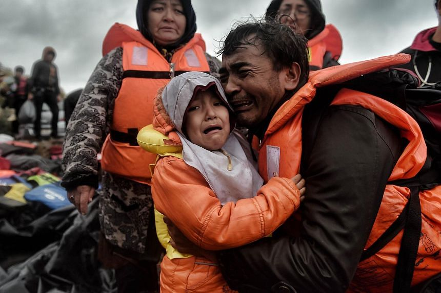 A man and his child crying as they scramble ashore on the Greek Island of Lesbos on Oct 14, after crossing the Aegean sea from Turkey.