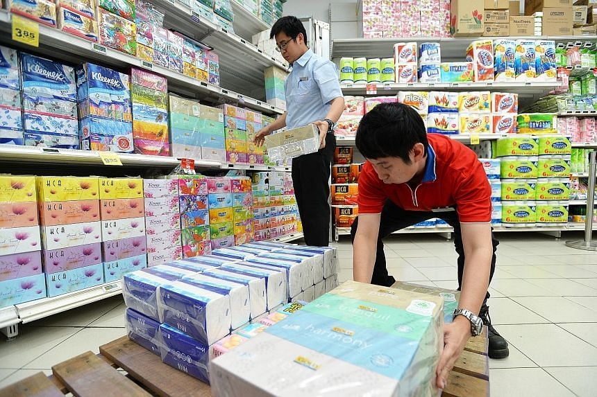 FairPrice employees William Lim (left) and Ong Wei Kiat removing APP products from the supermarket chain's nex outlet last month. APP has been accused of having fires on its concessions. Firefighters putting out a blaze in Banyuasin regency, South Su