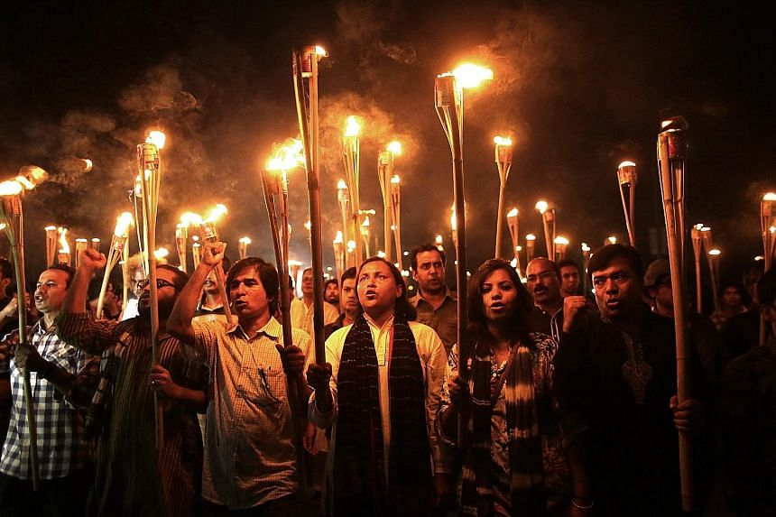 Cultural activists, writers and members of the secular movement Ganajagaran Mancha at a torchlit procession protesting against the killing and attacks on a publisher and bloggers in Dhaka, Bangladesh, on Monday. The group also called for a half-day c