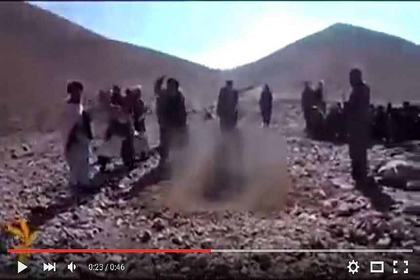 A screengrab from the graphic video showing the victim in a hole in the ground surrounded by men hurling stones at her.