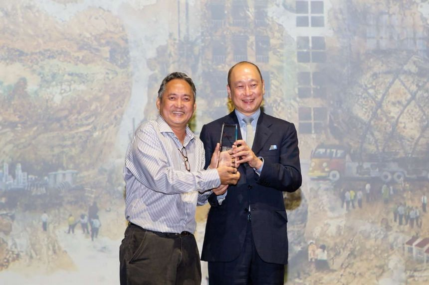 Mr Wee Ee Cheong (right), Deputy Chairman and CEO, UOB, presents Mr Benjamin F. Cruz with the 2015 UOB Painting of the Year, Singapore Award.