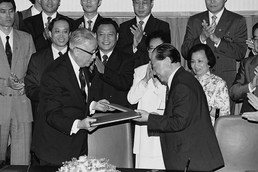 Taiwan's Koo Chen-fu (left) and China's Wang Daohan exchanging documents to sign at the conclusion of talks between the two sides in Singapore on April 29, 1993.