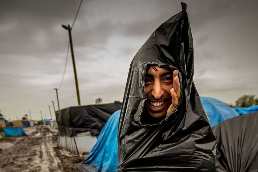 A migrant protects himself from the rain at a camp in Calais, France.