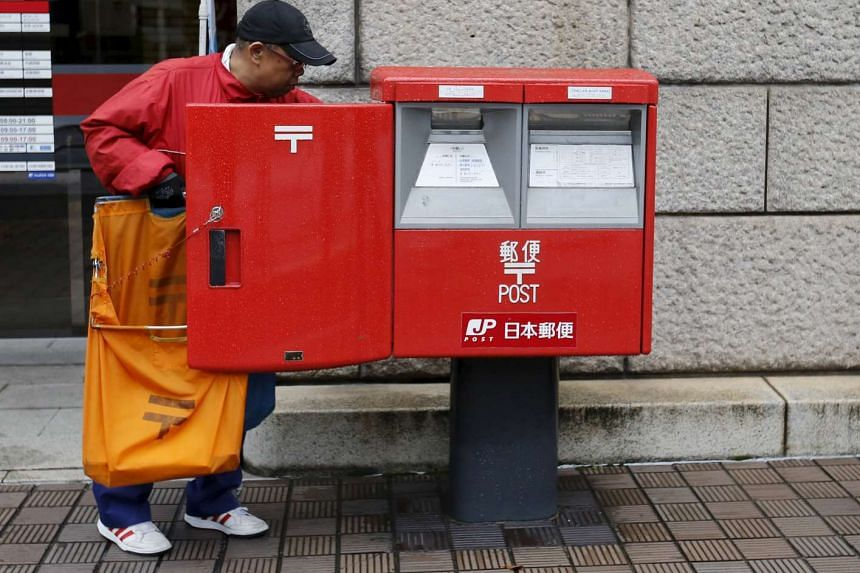 A worker of Japan Post Co collects postal items from a post box outside a post office in Tokyo.