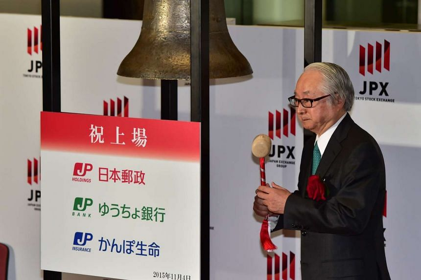 Japan Post Bank president Masatsugu Nagato rings a bell during the ceremony for the company's listing at the first sector of the Tokyo Stock Exchange on November 4, 2015. Japan Post made its long-awaited trading debut in Tokyo after an initial public
