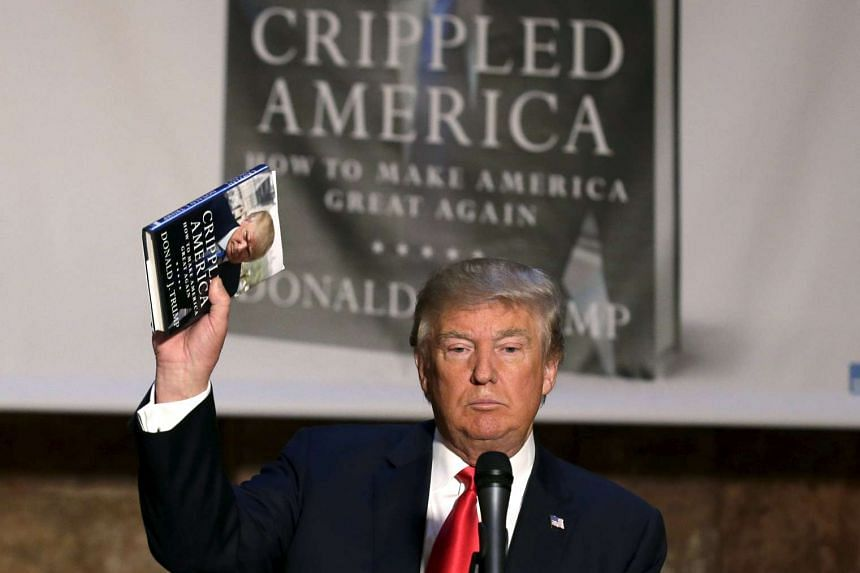 US Republican presidential candidate Donald Trump holds up a copy of his new book at news conference to promote it in New York City on Monday.