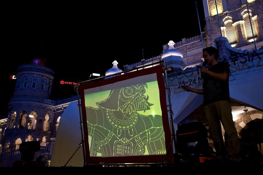 A distinctively Darth Vader-looking silhouette is projected on a screen as designer Chuo Yuan Ping, part of the team behind the Star Wars-inspired wayang kulit production, addresses the audience before a show at Independence Square in Kuala Lumpur.